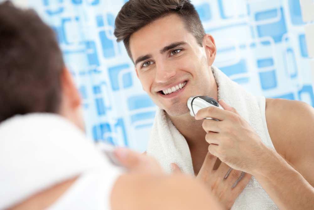 Mann vor Spiegel mit Elektrorasierer